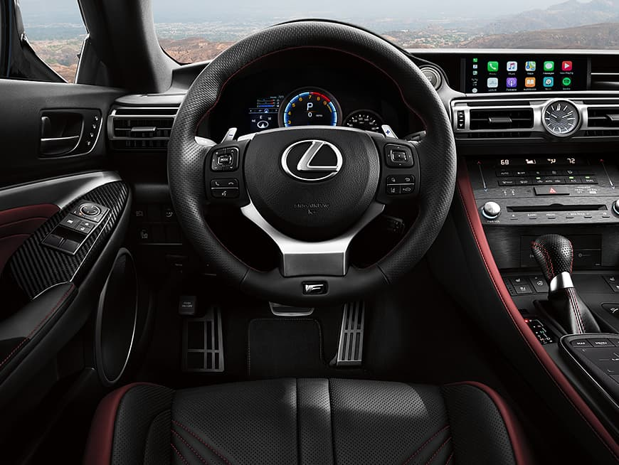 2020 RC F showing the race-inspired cockpit with the sport steering wheel and aluminum pedals.
