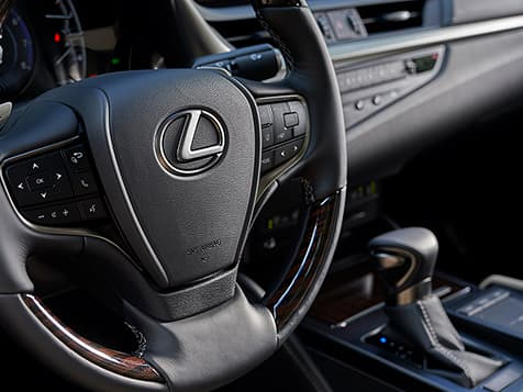 Interior shot of the 2019 Lexus ES shown with wood- and leather-trimmed steering wheel.