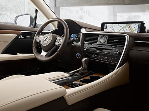 2019 Lexus RXL wood and leather steering wheel, middle console, navigation system and parchment leather seat detail as seen from the front passenger seat.