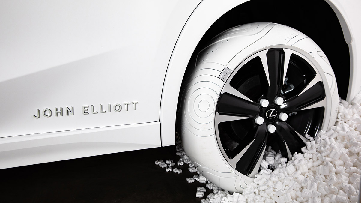LEXUS x JOHN ELLIOTT concept tires shown on an Ultra White Lexus UX with a JOHN ELLIOTT badge.