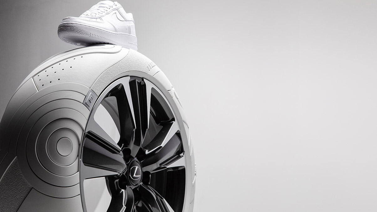 The iconic JOHN ELLIOTT x NIKE AF1 sneaker shown on top of the LEXUS x JOHN ELLIOTT concept tire.