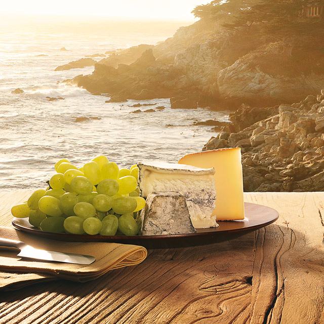 Food & Wine Owners Benefits displaying grapes and cheese on a table set overlooking the ocean.