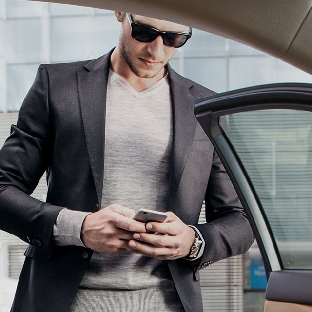 A man dressed in a suit looking down at his smart phone to view the Lexus App, an Owners Benefit.