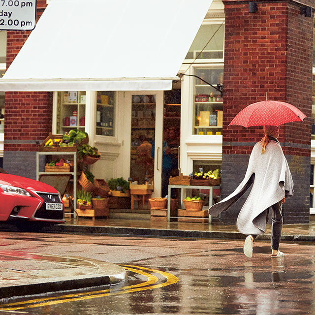 A woman walking on a street holding a red umbrella next to a red Lexus displays 'Retail Partners' as an Owners Benefit.