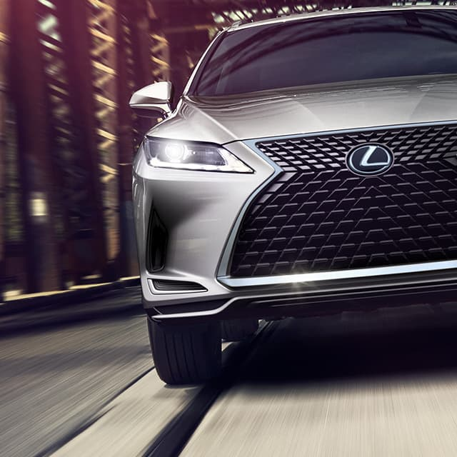 A silver Lexus sedan is shown in motion with a blurred background to display 'Warranty & Protection' as an Owners Benefit.