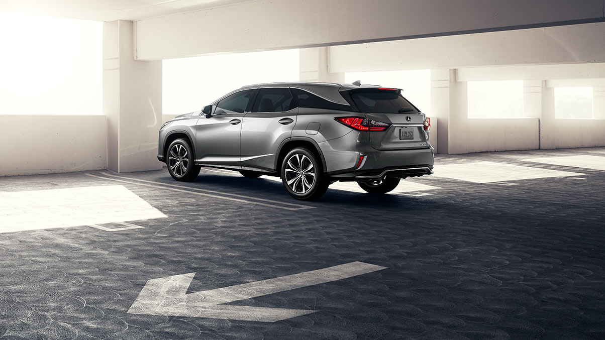 Rear, driver's side view of a 2019 RXL in Atomic Silver. The new Lexus seven-passenger luxury crossover is parked in garage with sunlight flooding in over the hood.