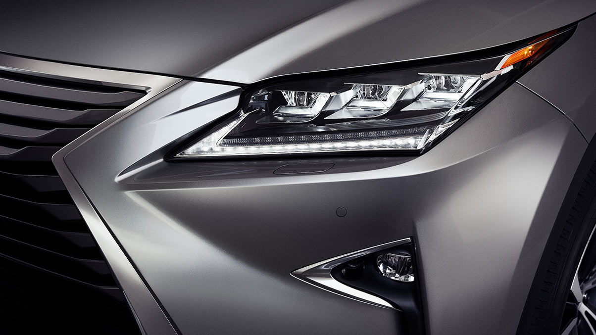 Close-up of the available driver side 2019 Lexus RXL headlights and hood. Shown in the Atomic Silver color option.