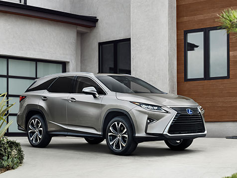 The new 2019 Lexus RXL sits parked in the driveway of a modern house. The two passenger side doors and wheels are visible along with the right headlight, bold grille and central metal Lexus emblem.